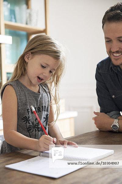 Vater beobachtet die junge Tochter beim Schreiben.