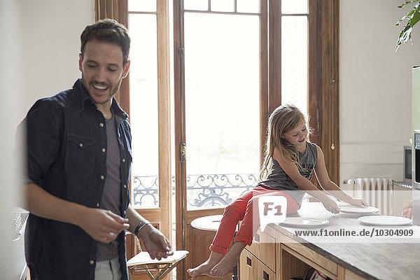 Mädchen hilft Vater  den Tisch für das Familienessen zu decken.
