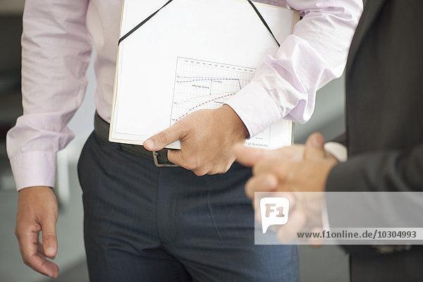 Geschäftsmann mit Dokumenten unterm Arm