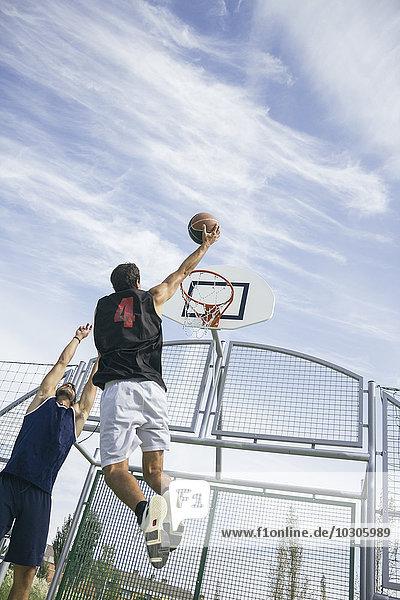 Junger Mann spielt Basketball  Dunking Ball