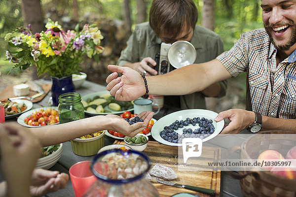 A group of friends gathered at a table outdoors  sharing dishes of fresh fruits and salads.