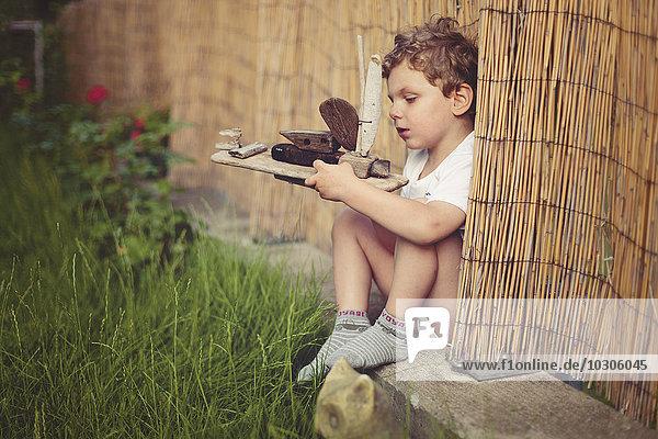 Kleiner Junge mit Holzschiff