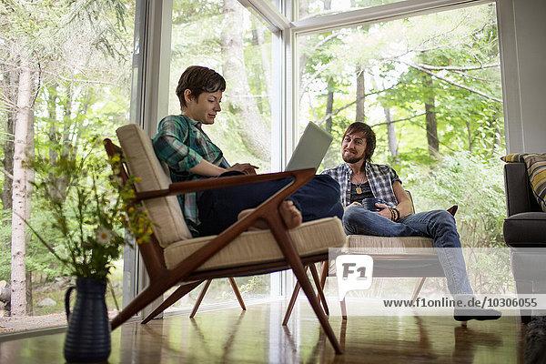 Ein Mann und eine Frau sitzen zusammen in einem Raum mit großen Bildfenstern  einer mit einem Laptop.
