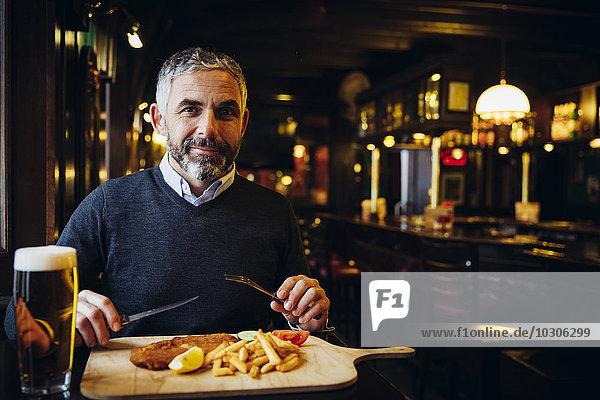 Lächelnder Mann im Restaurant mit Wiener Schnitzel und Pommes frites
