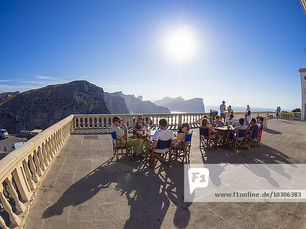 Spain  Mallorca  Cap Formentor  Young people sitting on terrace of the lighthouse