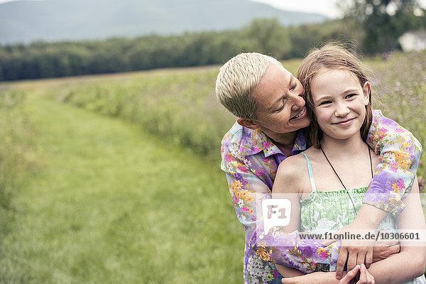 Eine reife Frau und ein junges Mädchen auf einer Wildblumenwiese.