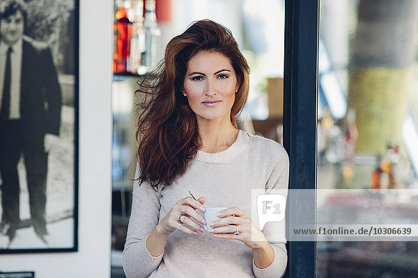 Smiling woman outdoors holding cup of coffee