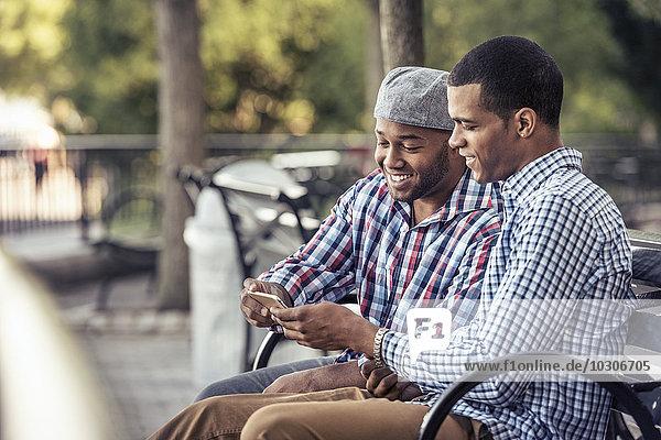 Two men sitting in a park  looking at a smart phone
