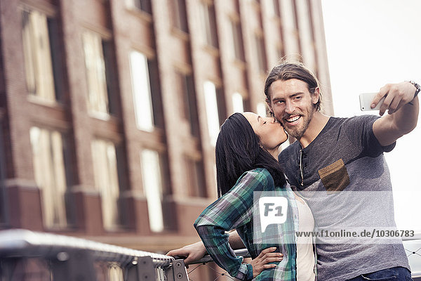A woman kissing a man on the cheek  posing for a selfie by a large city building