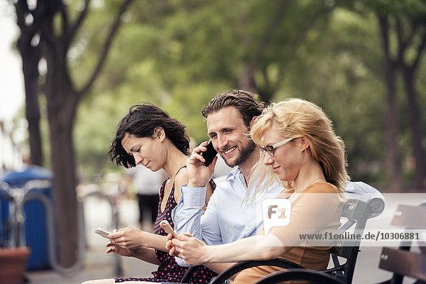 A man and two women seated on a bench in a park  checking their phones  one making a call.