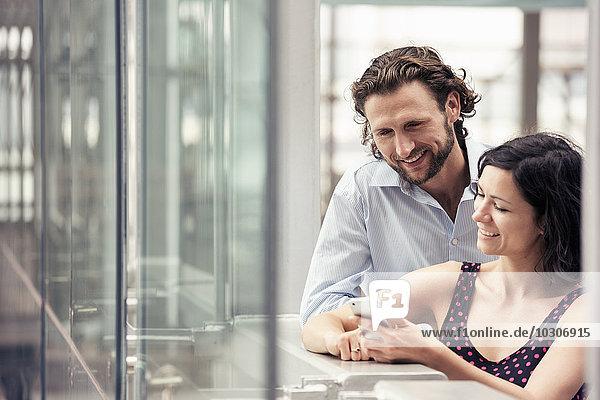 Ein Mann und eine Frau nebeneinander vor einem städtischen Gebäude  die auf ein Smartphone schauen