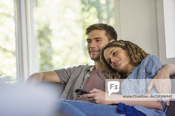 Ein Paar  ein Mann und eine Frau sitzen lachend nebeneinander und schauen auf einen Bildschirm.