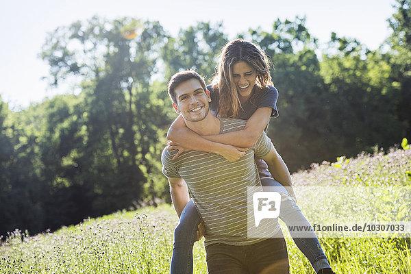 Ein Paar  ein Mann  der einer jungen Frau ein Huckepack gibt und im Sommer über eine Blumenwiese läuft.