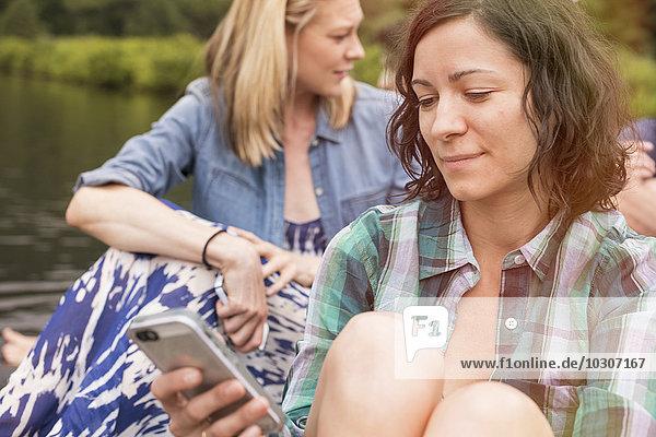 Eine Frau aus einer Gruppe  die im Sommer ihr Smartphone benutzt.