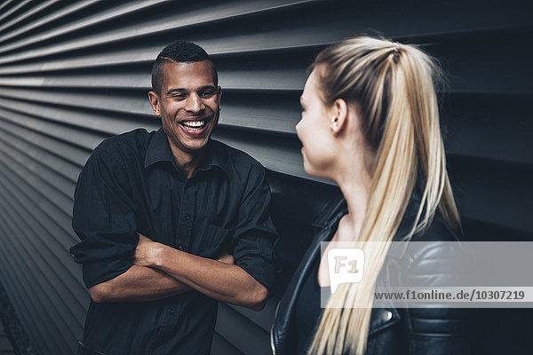 Schwarz gekleideter junger Mann von Angesicht zu Angesicht mit junger Frau vor schwarzer Fassade