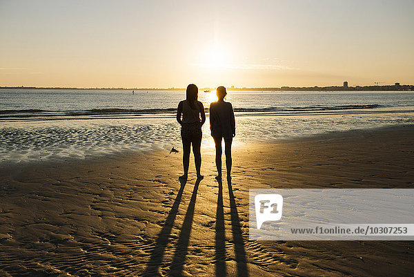 France  Pornichet  silhouettes of two women standing on the beach at sunset
