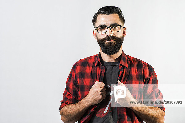 Portrait of hipster in front of light background