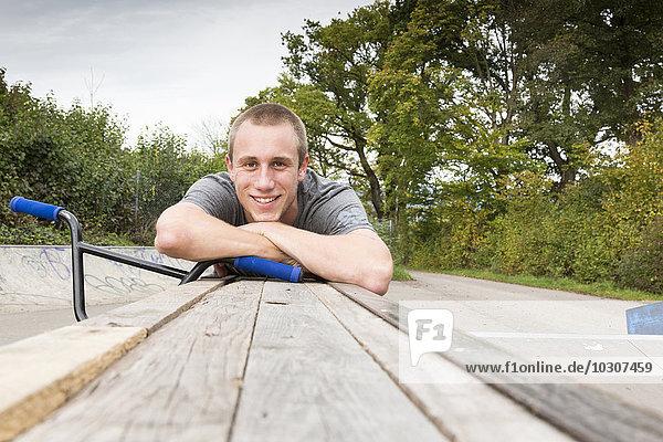Porträt eines lächelnden jungen Mannes mit verschränkten Armen