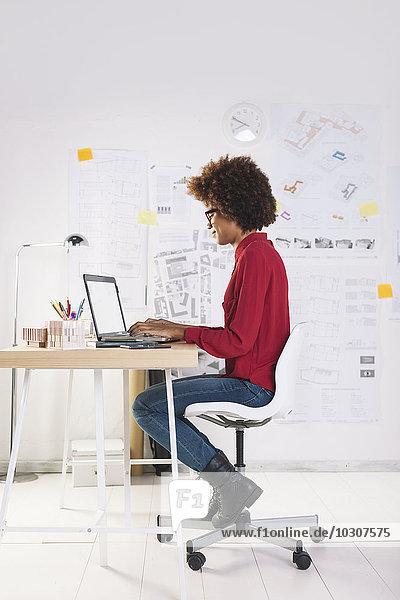Junge Architektin mit Laptop im Büro