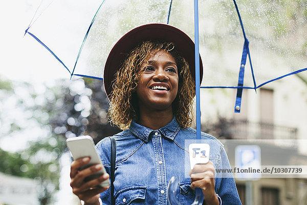 Spanien  Barcelona  Portrait einer lächelnden jungen Frau mit Schirm und Smartphone