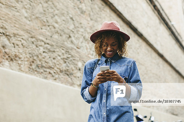 Portrait of smiling young woman wearing hat and denim shirt looking at smartphone