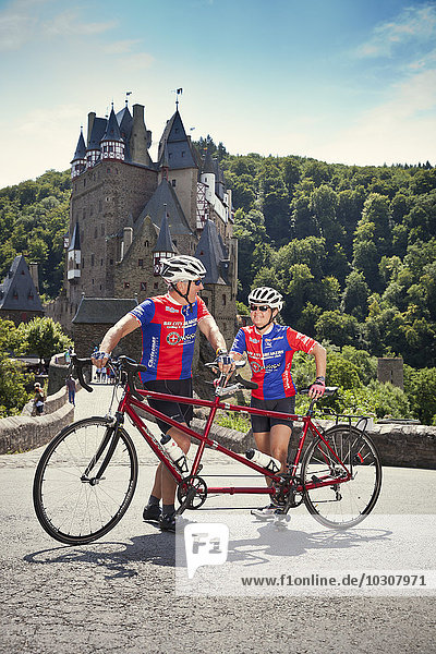 Germany  Rhineland-Palatinate  US American couple standing in front of Eltz Castle with their tandem