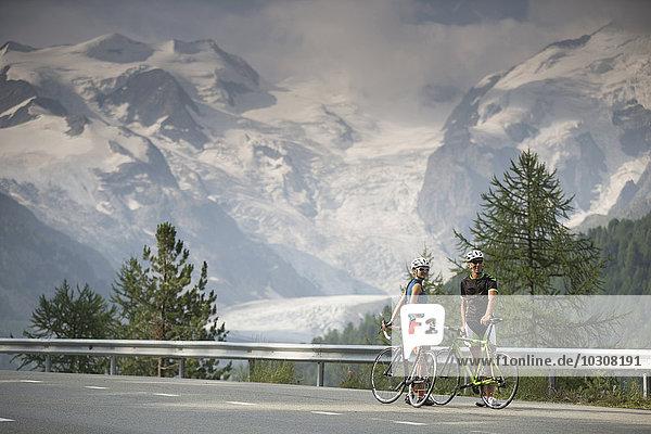 Schweiz  Engadin  zwei Radfahrer auf der Berninapassstrasse vor dem Morteratschgletscher