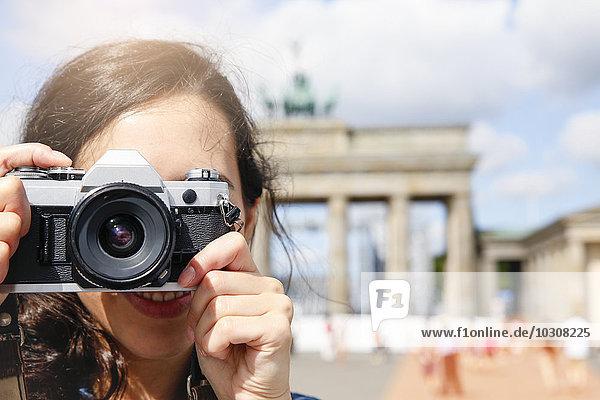Deutschland,  Berlin,  Touristin vor dem Brandenburger Tor fotografiert Zuschauerin