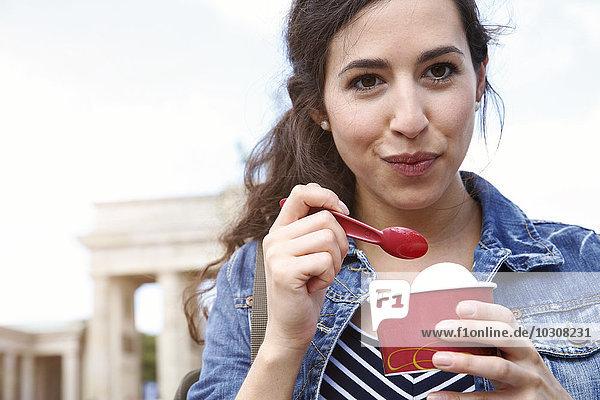 Deutschland  Berlin  Porträt einer jungen Touristin beim Eisessen am Brandenburger Tor