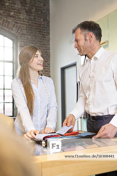 Junge Frau hilft dem Kunden bei der Wahl der Krawatte