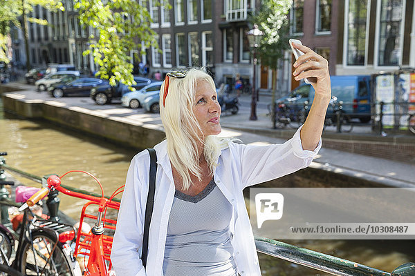 Niederlande  Amsterdam  Seniorenfrau am Stadtkanal