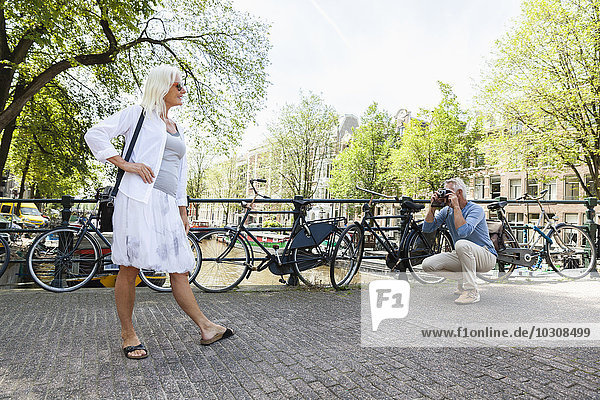 Niederlande  Amsterdam  älterer Mann fotografiert Frau auf der Brücke