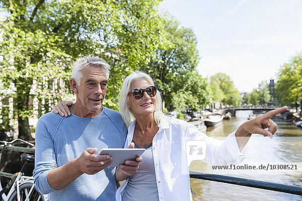Niederlande  Amsterdam  Seniorenpaar mit digitalem Tablett am Stadtkanal
