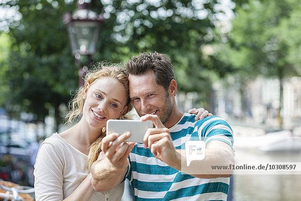 Niederlande  Amsterdam  lächelndes Paar  das einen Selfie am Stadtkanal nimmt.