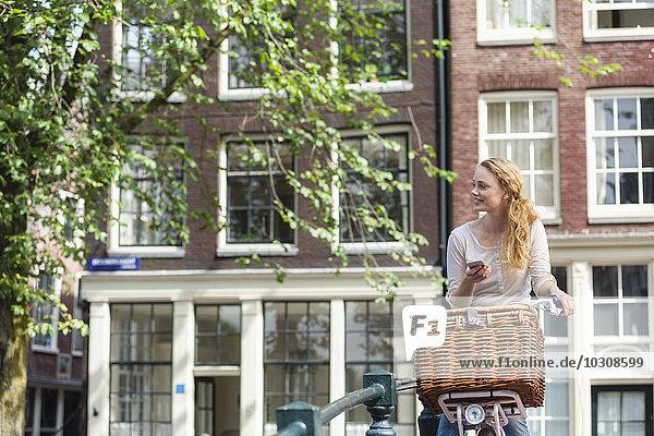 Niederlande  Amsterdam  Frau mit Fahrrad und Handy in der Stadt