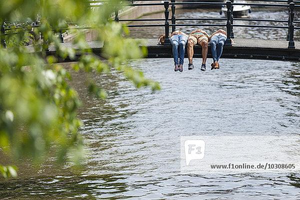 Niederlande  Amsterdam  drei Freunde auf der Brücke am Stadtkanal liegend