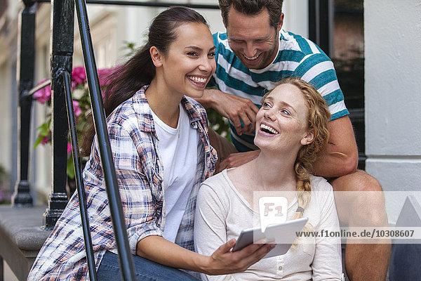 Niederlande  Amsterdam  drei glückliche Freunde sitzend mit digitalem Tablett vor der Haustür