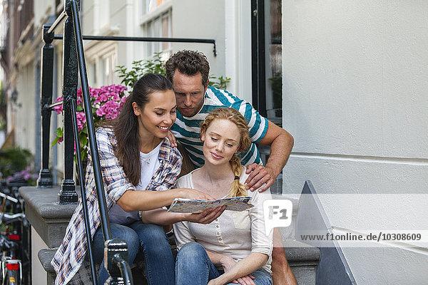 Niederlande  Amsterdam  drei Freunde sitzend mit Karte vor der Haustür
