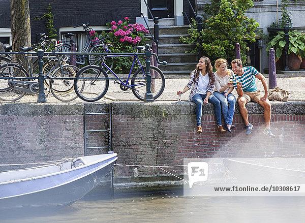 Niederlande  Amsterdam  drei glückliche Freunde sitzen mit Getränken am Stadtkanal