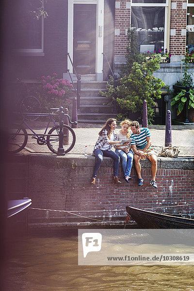Niederlande  Amsterdam  drei Freunde sitzend mit digitalem Tablett am Stadtkanal