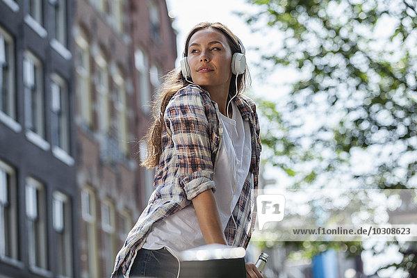 Niederlande  Amsterdam  junge Frau mit Kopfhörer und Bierflasche im Freien