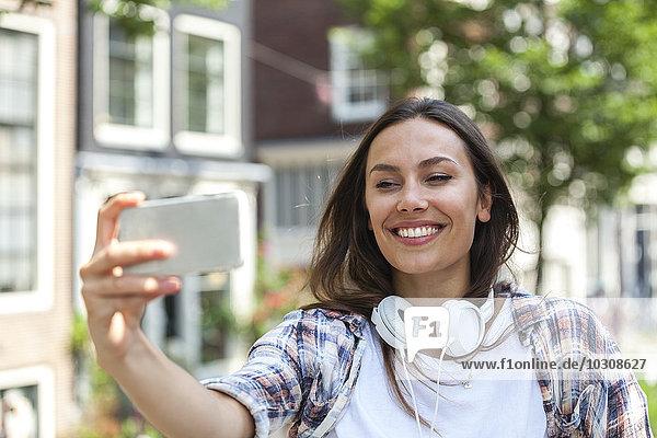 Niederlande  Amsterdam  lächelnde junge Frau mit einem Selfie