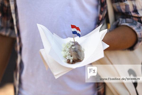 Frau hält Serviette mit Matjeshering und holländischer Flagge