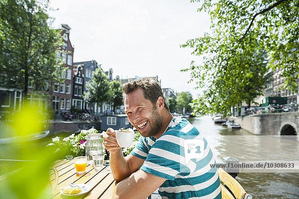 Niederlande  Amsterdam  glücklicher Mann beim Kaffeetrinken am Stadtkanal