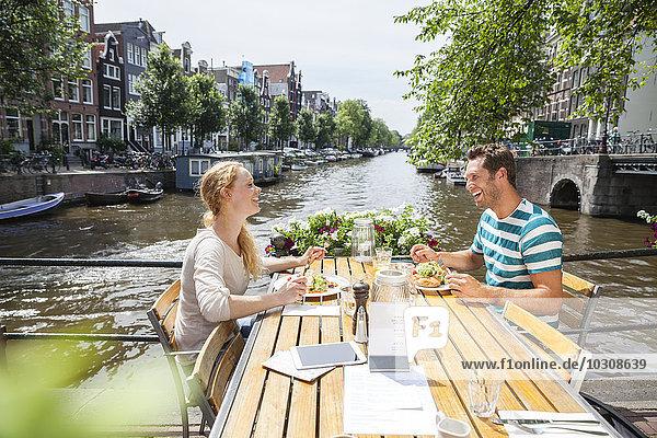 Niederlande  Amsterdam  glückliches Paar beim Mittagessen am Stadtkanal