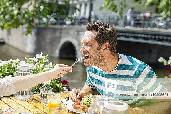 Niederlande  Amsterdam  Frau füttert Mann im Außenrestaurant am Stadtkanal