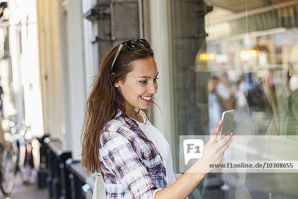 Niederlande  Amsterdam  lächelnde junge Frau in der Stadt mit Blick auf das Handy