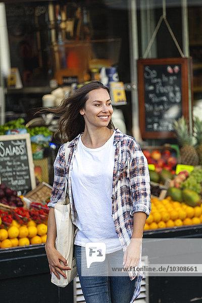 Lächelnde junge Frau im Gemüseladen