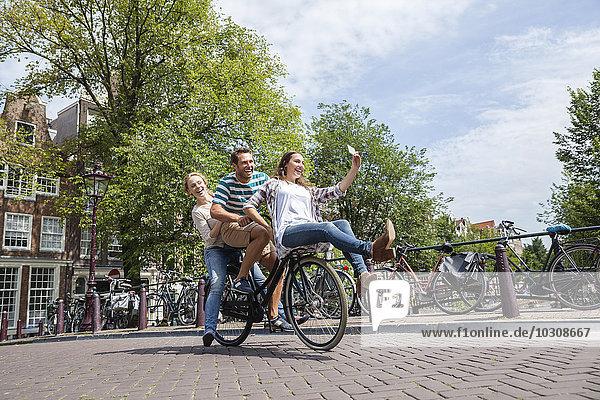 Niederlande  Amsterdam  drei verspielte Freunde auf einem Fahrrad in der Stadt