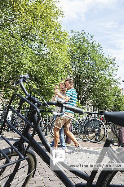 Niederlande  Amsterdam  glückliches Paar tanzend in der Stadt